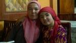 Niña uigur junto a su madre en un restaurante de Kashgar