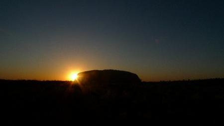 El sol aparece un día mas tras la roca de Ulurú. Espectacular.